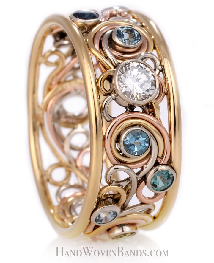 This is a mothers ring made with a swirl ring. It has many gemstones added to it and is an artistic family ring handmade by an artist.