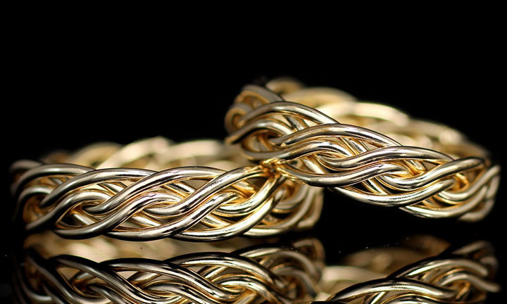 A set of braided wedding rings woven together from one braid. It is in solid 14k yellow gold and a black background. This unique wedding ring is braided by Todd Alan.