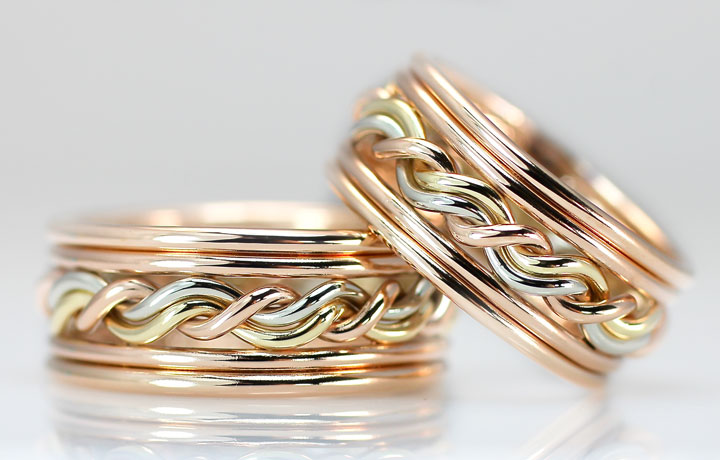 These are double outer bands, both in 14k rose gold with a tri-tone braided ring in the center. These braided wedding rings are made by hand by artist Todd Alan