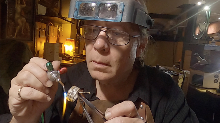 Todd Alan using a torch to make a ring by hand. Todd handmakes all his braided wedding rings. Artist Todd Alan making a ring.
