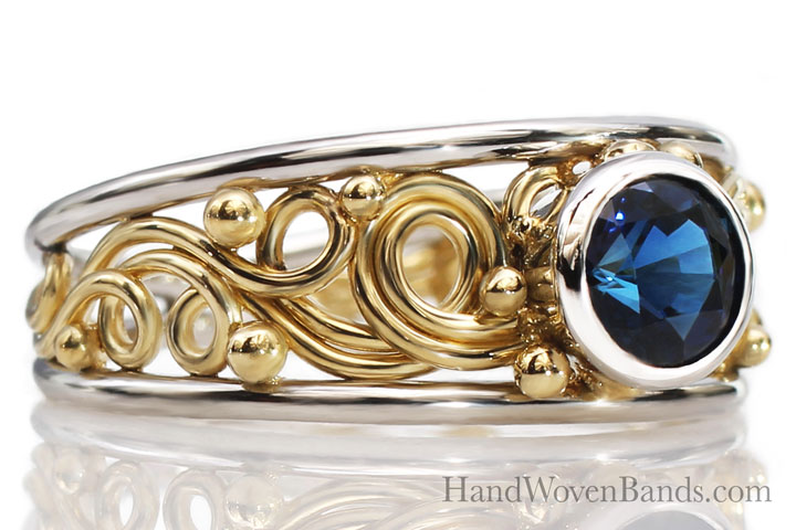 This swirl ring is a tapered artisan ring mounted with a sapphire ring. This ring was handmade by Todd Alan and is a very unique 14k yellow gold ring handmade by artist Todd Alan