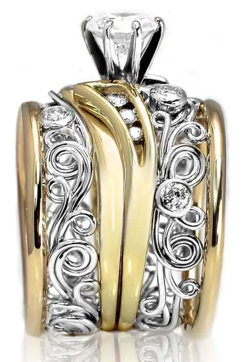 This unique artisan ring was handmade by Todd Alan. It is set with diamonds and uses swirl ring patterns and Filigree work. Its truly a masterwork ring.